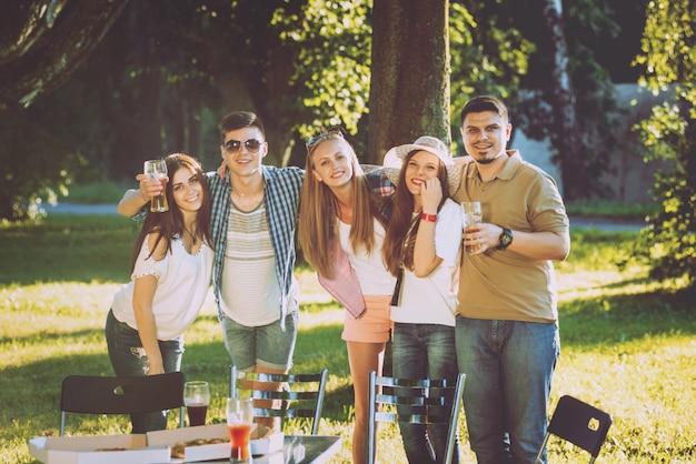 Vrolijke vrienden op picknick in het park. pizza eten Premium Foto