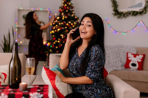 Vrolijke vrij jong meisje praat over telefoon zittend op een stoel en haar vriend versiert kerstboom genieten van kersttijd thuis Gratis Foto