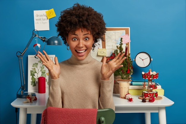 Vrolijke vrolijke vrouw met donkere huid heeft beide handpalmen omhoog, zit op het bureaublad met een kerstboom en andere vakantieattributen Gratis Foto