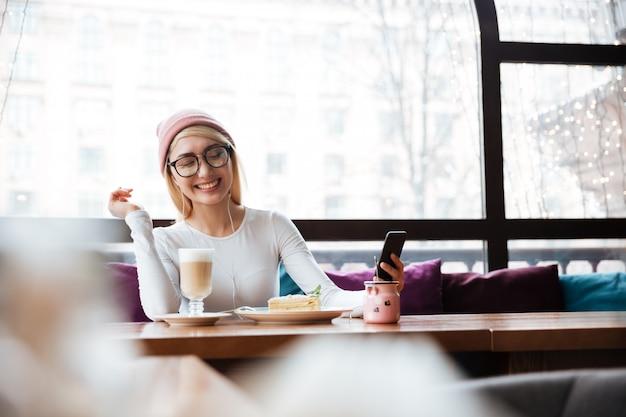Vrolijke vrouw die aan muziek van celtelefoon luistert in koffie Gratis Foto