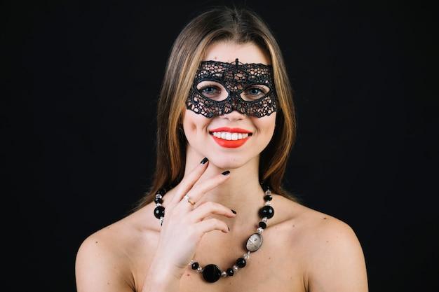 Vrolijke vrouw die carnaval-masker en halsband over zwarte achtergrond draagt Gratis Foto