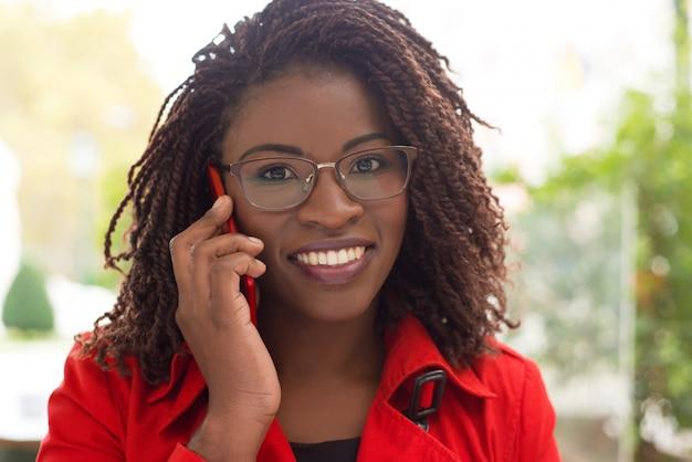 Vrolijke vrouw die door mobiele telefoon spreekt Gratis Foto