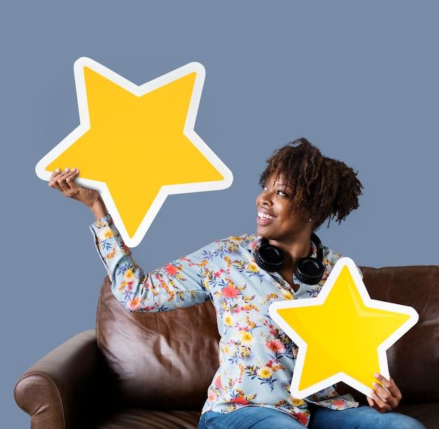Vrolijke vrouw die gouden sterrenpictogrammen houdt Gratis Foto