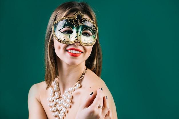 Vrolijke vrouw die groen carnaval-masker en halsband draagt Gratis Foto