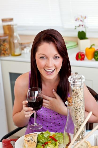 Vrolijke vrouw die haar maaltijd eet die een glas wijn thuis houdt Premium Foto