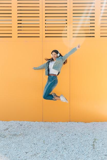 Vrolijke vrouw die tegen muur springt die haar wapens outstretching Gratis Foto