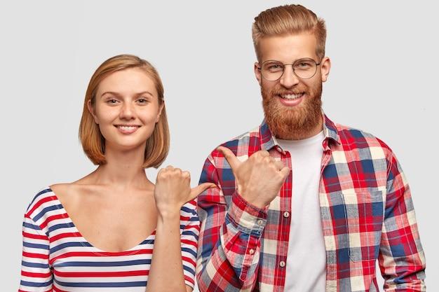 Vrolijke vrouw en man beste vrienden wijzen naar elkaar, glimlachen vriendelijk op gezichten, trekken aandacht Gratis Foto