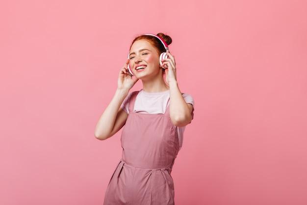Vrolijke vrouw gekleed in lichte overall dansen en luisteren naar muziek op koptelefoon op roze achtergrond. Gratis Foto
