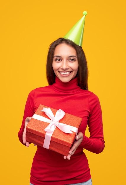 Vrolijke vrouw in rode coltrui en groene feestmuts glimlachend voor camera en demonstreren aanwezig tijdens verjaardagsviering tegen gele achtergrond Premium Foto