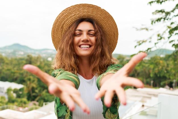 Vrolijke vrouw in stro hoed, met plezier, strekt de handen naar de camera. Gratis Foto