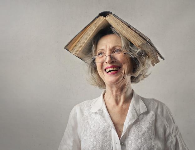 Vrolijke vrouw, lachend met een boek op haar hoofd Gratis Foto