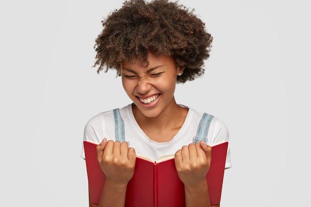 Vrolijke vrouw lacht vrolijk terwijl ze een grappig verhaal uit een boek leest, witte tanden laat zien, gezicht loenst als een glimlach, gekleed in een casual outfit, geïsoleerd over een witte muur. mensen, hobby en lezen concept Gratis Foto