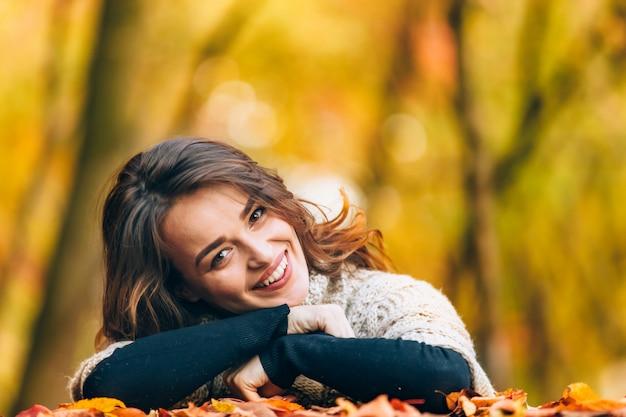 Vrolijke vrouw met geleund hoofd naar de zijkant glimlacht herfst landschap Premium Foto