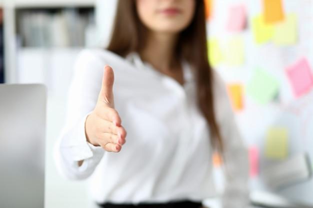Vrolijke vrouwelijke bediende die zakenpartner welkom heet Premium Foto
