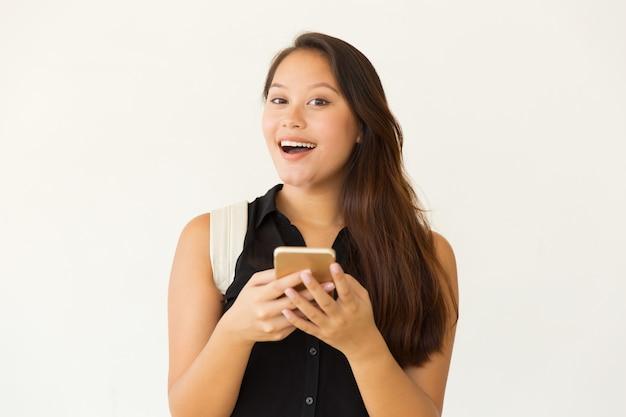 Vrolijke vrouwelijke student die smartphone gebruikt Gratis Foto