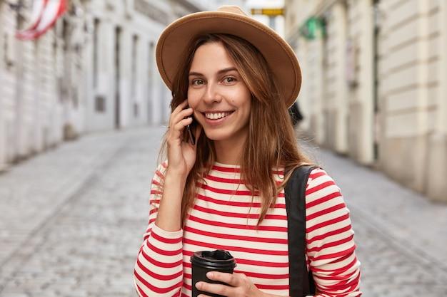 Vrolijke vrouwelijke toerist vormt in de stedelijke ruimte, drinkt afhaalkoffie in papieren beker Gratis Foto
