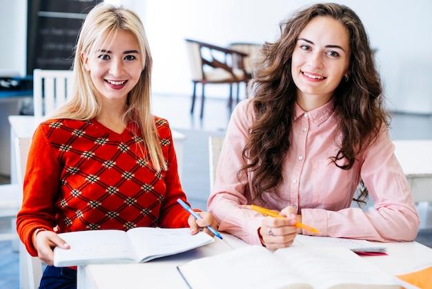 Vrolijke vrouwen die aan examen voorbereidingen treffen   Gratis Foto