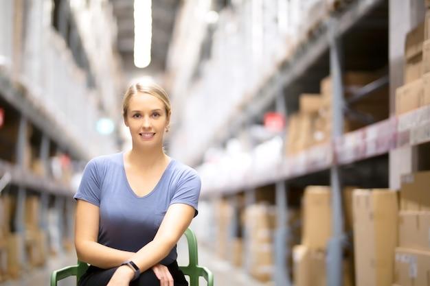 Vrolijke vrouwenklant die camera bekijken en op stoel zitten terwijl het winkelen in ijzerhandel Premium Foto