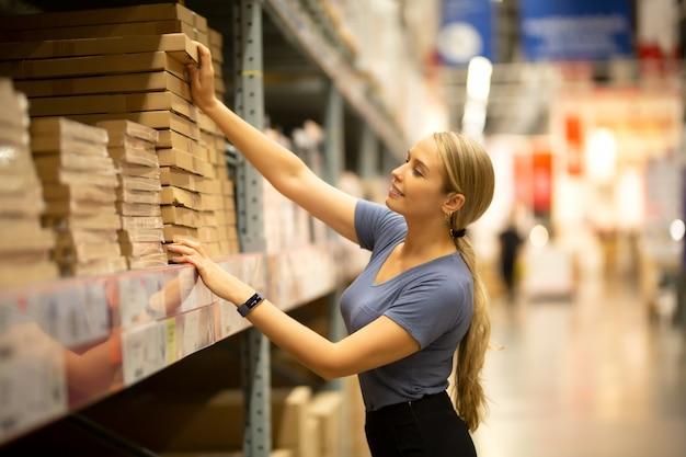 Vrolijke vrouwenklant die omhooggaand en product op plank trekken kijken terwijl het winkelen in ijzerhandel Premium Foto