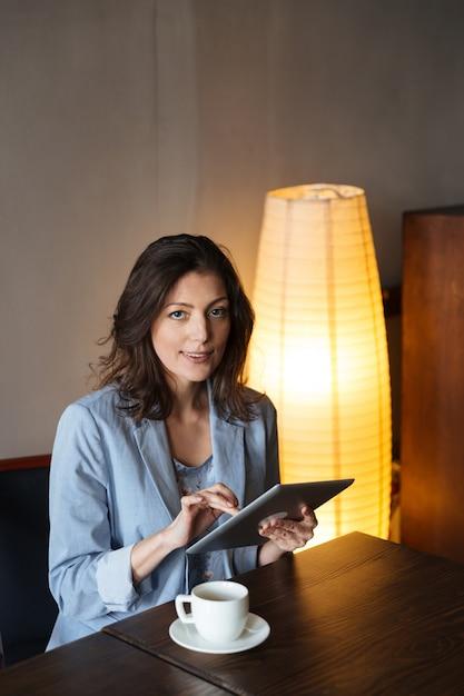 Vrolijke vrouwenzitting die binnen tabletcomputer met behulp van. Gratis Foto