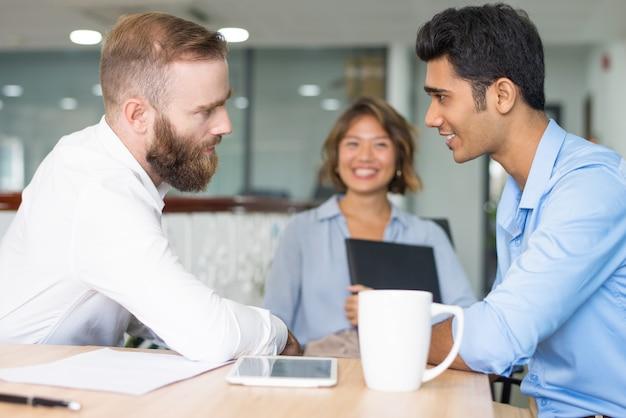 Vrolijke werknemer die aan het fronsen van werkgever rapporteert Gratis Foto