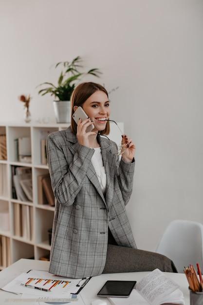 Vrolijke zakelijke dame glimlacht tijdens het communiceren via de telefoon. vrouw in grijs geruit jasje poseren in wit kantoor. Gratis Foto