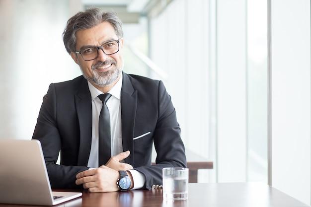 Vrolijke zakenman in bril in kantoor Gratis Foto