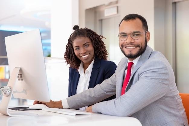 Vrolijke zakenmensen met behulp van desktop computer Gratis Foto