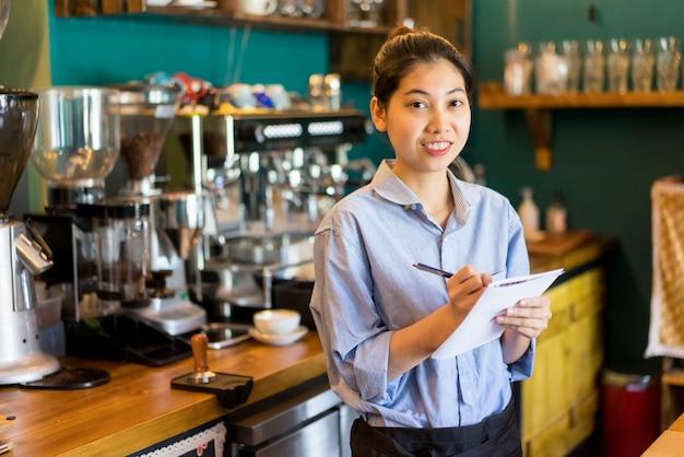 Vrolijke zekere aziatische serveerster die nota's in document maakt. Premium Foto