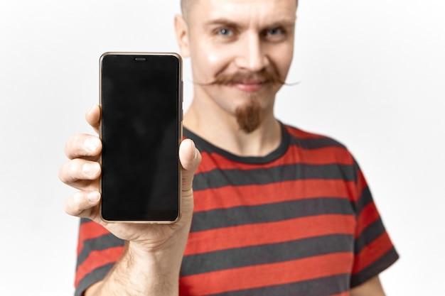 Vrolijke zelfverzekerde jonge beaded man glimlachend gelukkig, moderne gloednieuwe zwarte mobiele telefoon demonstreren met perfect design en copyspace display. selectieve aandacht aan kant met elektronisch apparaat Gratis Foto