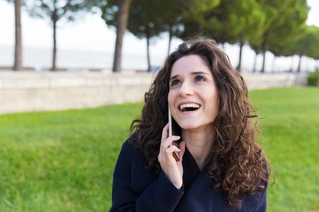 Vrolijke zorgeloze vrouw die van prettig telefoongesprek geniet Gratis Foto