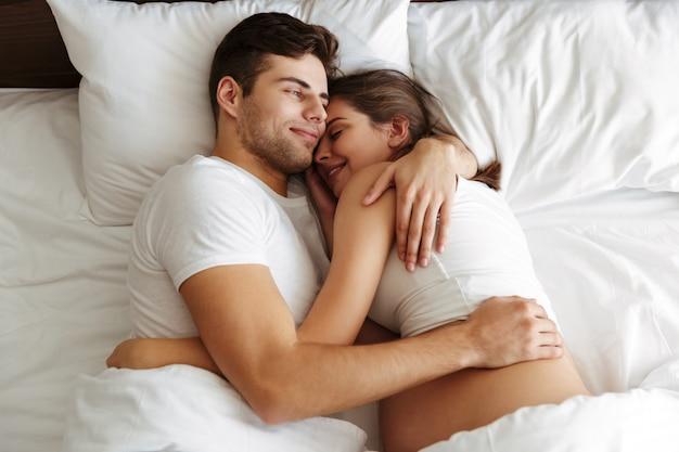 Vrolijke zwangere vrouw ligt in bed met echtgenoot Gratis Foto