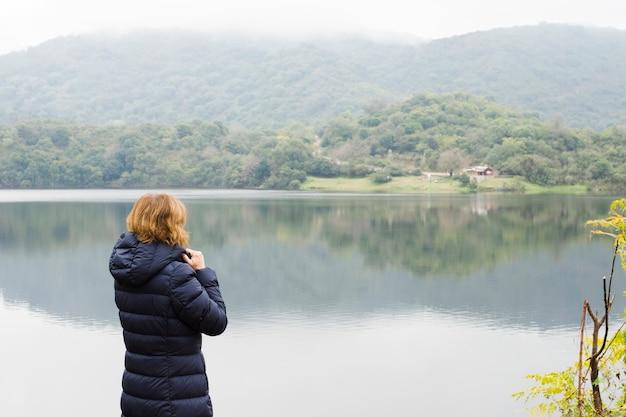 Vrouw aan het meer genieten van het uitzicht Gratis Foto