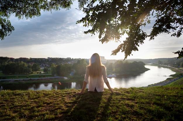 Vrouw aanbrengen op het gras, ontspannen en genieten van het uitzicht op de rivier Premium Foto