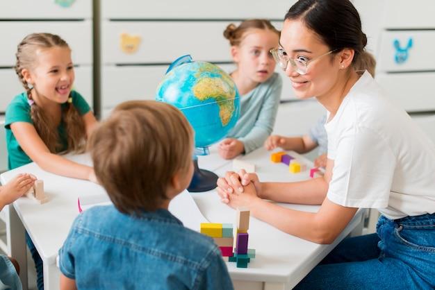 Vrouw aardrijkskunde onderwijzen aan kinderen Premium Foto