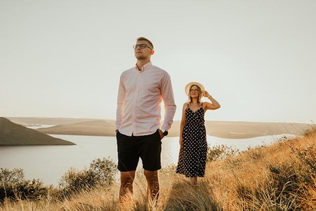 Vrouw achter man in stralen van de ondergaande zon in de zomer in de buurt van meer Premium Foto