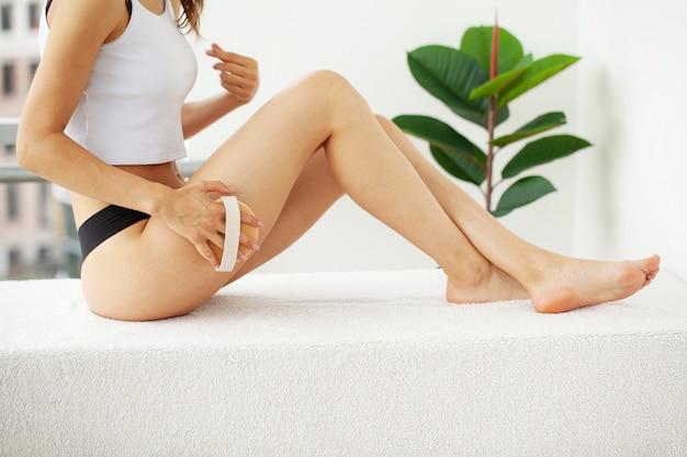 Vrouw arm met droge borstel boven haar been, cellulitis behandeling en droog borstelen. Premium Foto