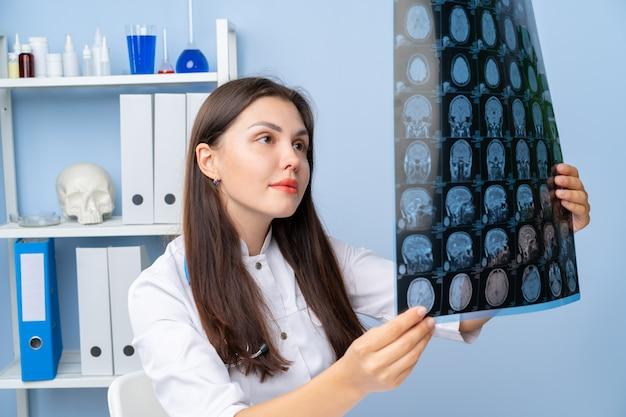 Vrouw arts die het beeld van mr van de patiënt in haar bureau onderzoeken Premium Foto