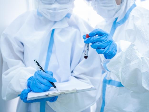 Vrouw arts die masker draagt en reageerbuis houdt alvorens bloedmonster van patiënt voor onderzoek coronavirus te verzamelen. medisch en gezondheidszorgconcept. Premium Foto