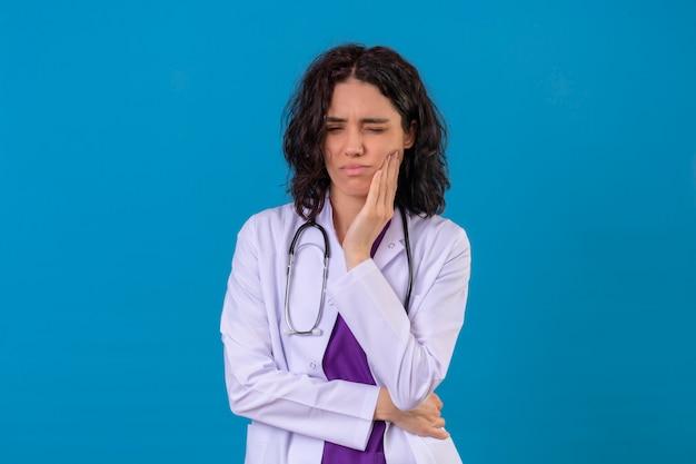 Vrouw arts dragen witte jas met een stethoscoop staan met de hand op de wang lijden vorm kiespijn op geïsoleerde blauw Gratis Foto