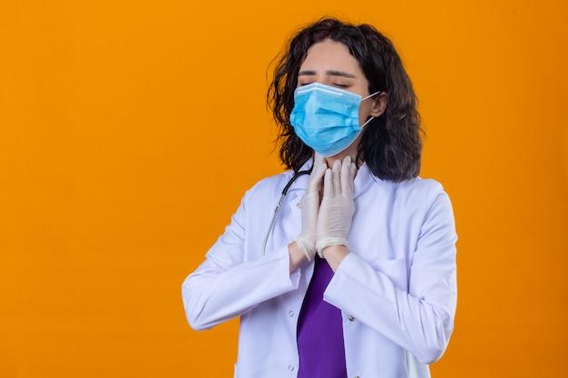 Vrouw arts dragen witte jas met stethoscoop in medische beschermend masker op zoek onwel aanraken van nek pijn lijden staande op geïsoleerde oranje Gratis Foto
