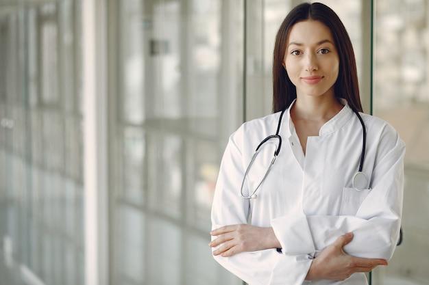 Vrouw arts in een witte uniforme status in een zaal Gratis Foto