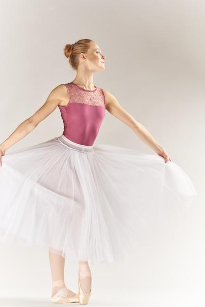 Vrouw ballerina in pointe-schoenen en in een tutu op een lichte achtergrond vormt poseren benen dansmodel Premium Foto