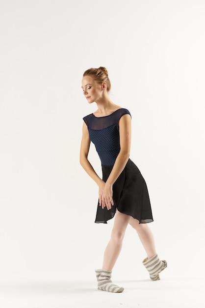 Vrouw ballerina rekt zich uit in de studio Premium Foto