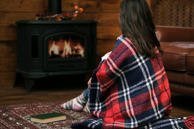 Vrouw bedekt met deken naast open haard Gratis Foto