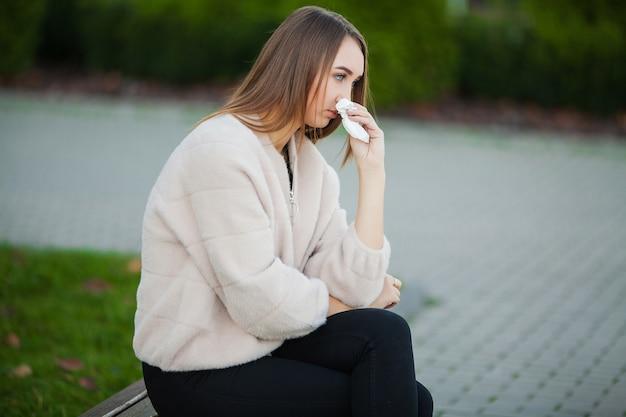 Vrouw benadrukt van het werk zittend buiten, pers van collega's Premium Foto