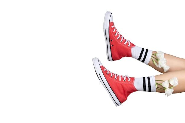 Vrouw benen in stijlvolle rode sneakers en witte sokken met bloemen Premium Foto