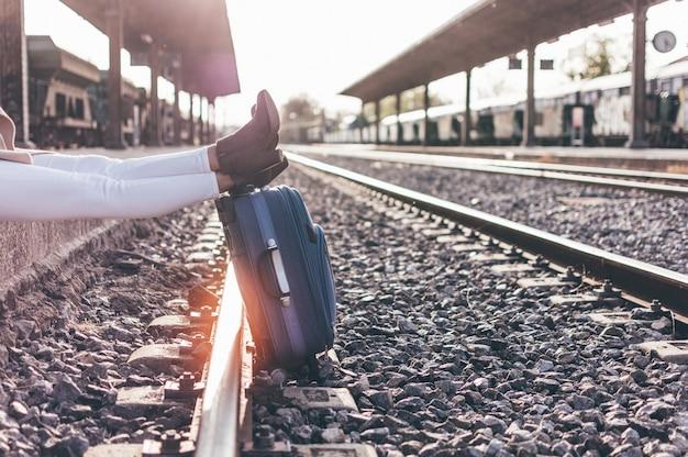 Vrouw benen leunend op een koffer op een treinstation in de schemering. Premium Foto