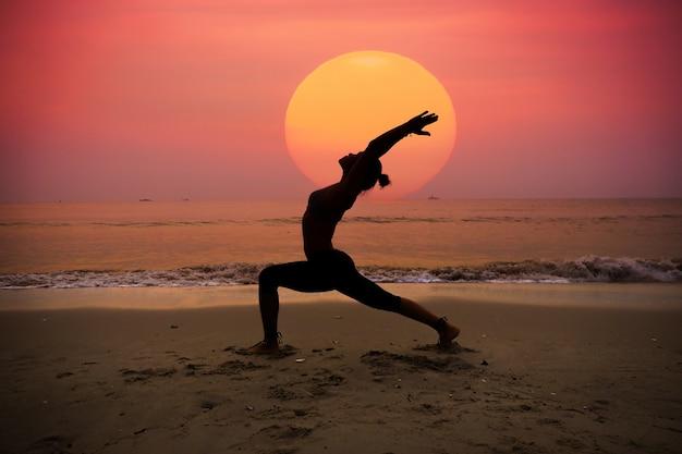 Vrouw beoefenen van yoga met de zon achter haar Gratis Foto