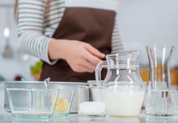 Vrouw bereidt bakkerijingrediënten op aanrechttafel in de keuken met het water van het melkei en bloem. Premium Foto